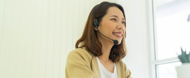 Close up young call center employee woman talking with colleagues and partner at desktop