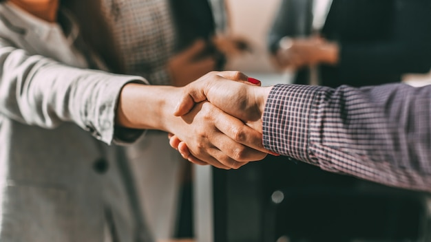 Крупным планом молодых случайных деловых людей, пожимая друг другу руки