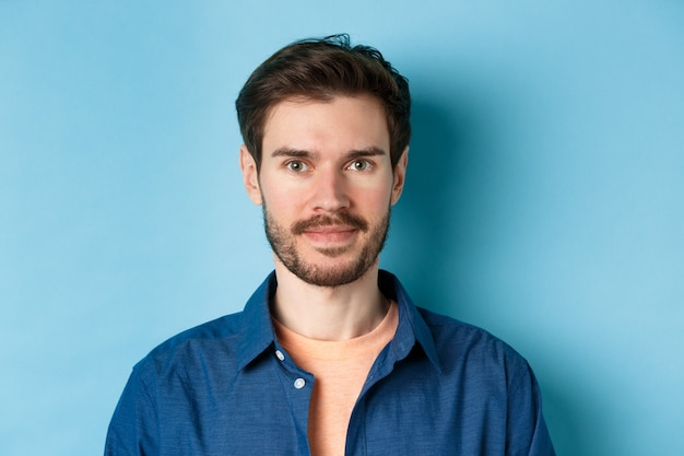 Close-up of young caucasian guy with beard smiling at looking happy at camera, standing on blue background.