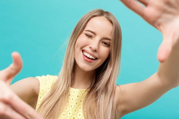 클로즈업 젊은 백인 여성의 얼굴과 눈 관리와 그녀는 파스텔 파란색 배경 위에 격리된 손으로 프레임을 만들고 있습니다.