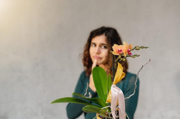 노란색 화분에 심은 난초 식물을 들고 젊은 백인 여자를 닫습니다.