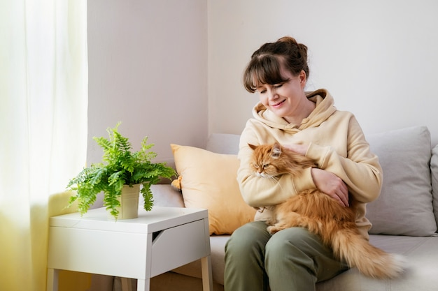 Close up of young caucasian woman sitting on sofa with ginger cat. comfort home zone.