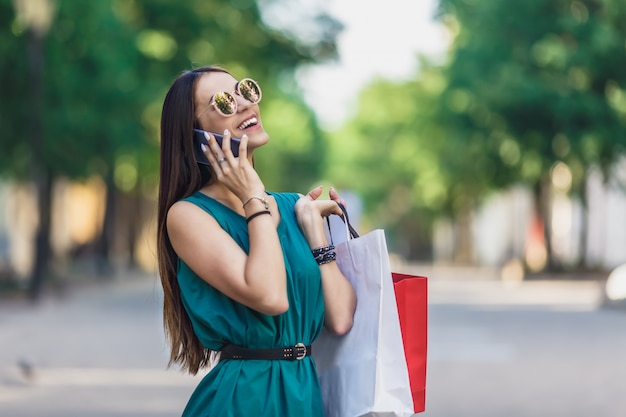 Close up of young charming dark-haired caucasian female with shopping bags smiling with teeth and talking on phone