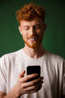 Close-up of young cheerful redhead bearded young man, listening music with airpods