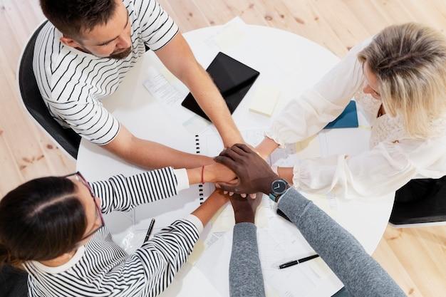 Primo piano sulle mani dei giovani colleghi in una riunione Foto Gratuite