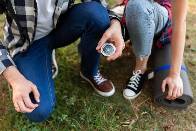 Giovani coppie del primo piano che controllano la bussola