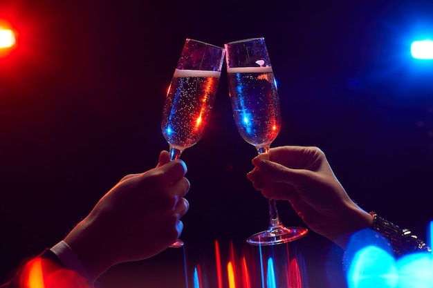 Close up of young couple clinking champagne glasses lit by party lights against black background, copy space