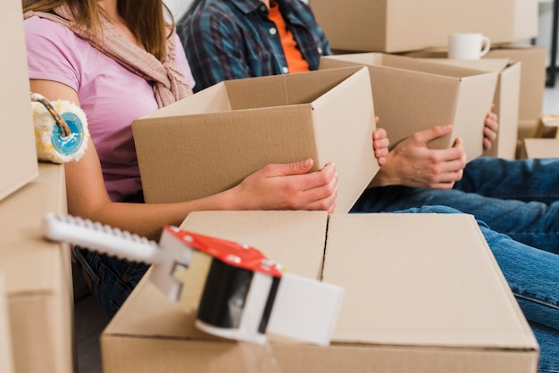Close-up of young couple holding cardboard boxes in hand at their new house