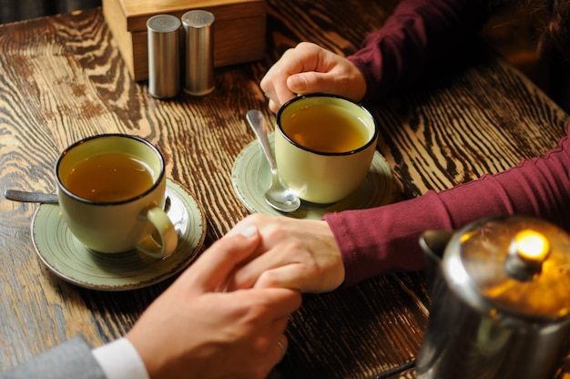 Close up of the young couple holding hands in a cafe and drinking tea romantic cozy time in evening