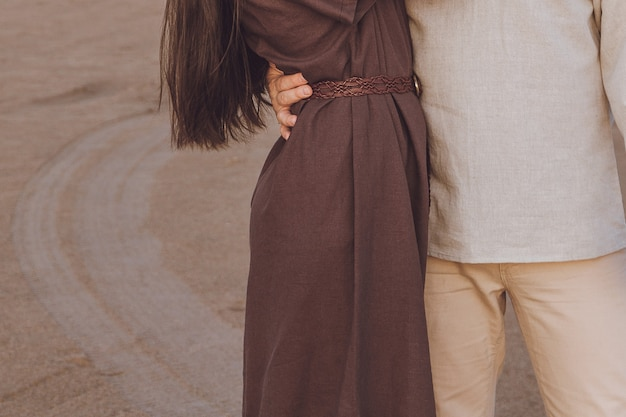Close-up of young couple hugging outdoor. family look linen clothes.