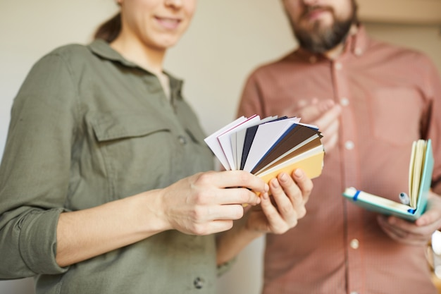 Close up of young couple looking at color samples standing by white blank wall while redecorating house, copy space