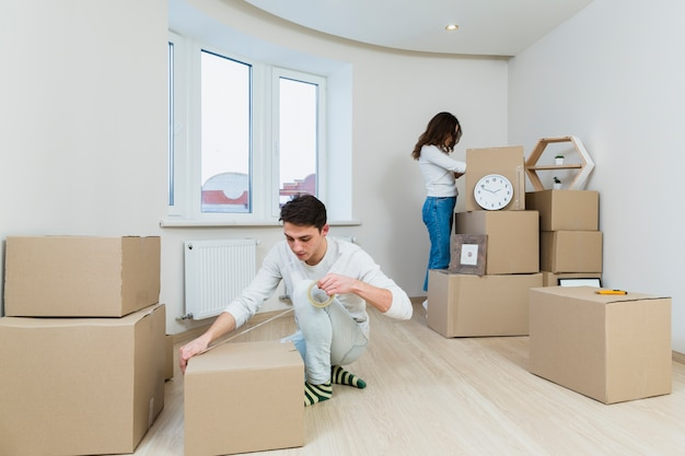 Close-up of young couple packing the cardboard box at home