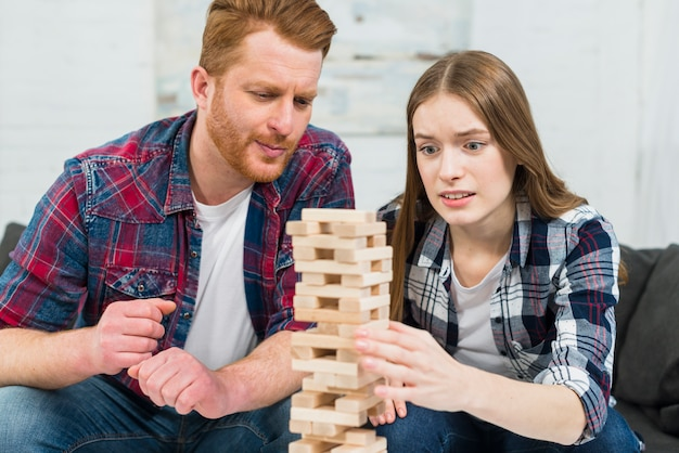 Close-up of young couple playing the wooden block tower