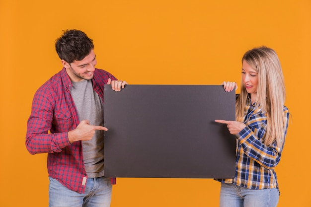 Close-up of young couple pointing their fingers on the black placard against an orange background