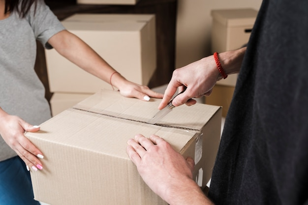 Close-up young couple preparing cardboard boxes to move