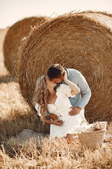 Primo piano di una giovane coppia seduta al campo di grano. la gente si siede sul pagliaio sul prato e si abbraccia.