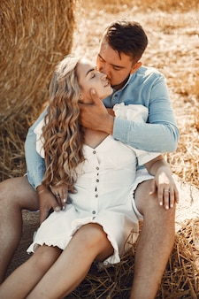 Close up of a young couple sitting at the wheat field. people sits on haystack on meadow and embraces.