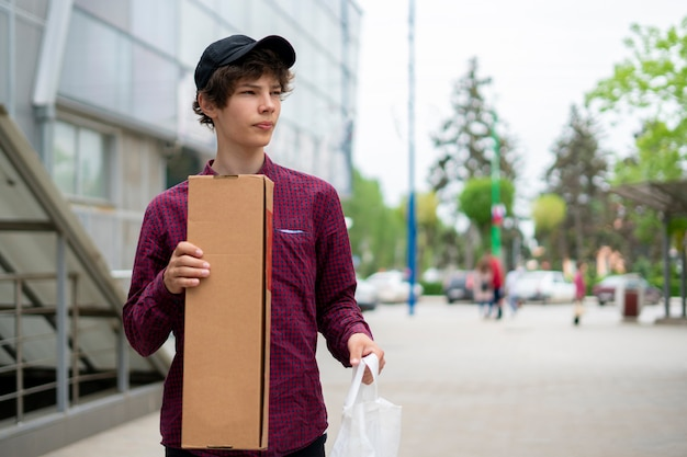Close up young courier waiting for a client customers in the city