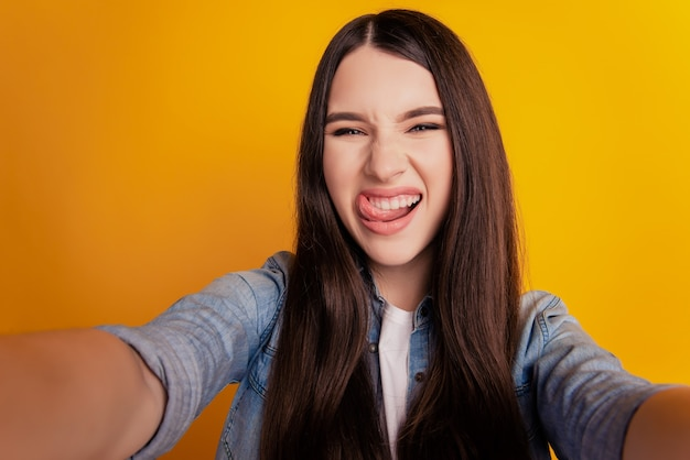 Close-up of young crazy funky woman taking selfie stick-out tongue on yellow background