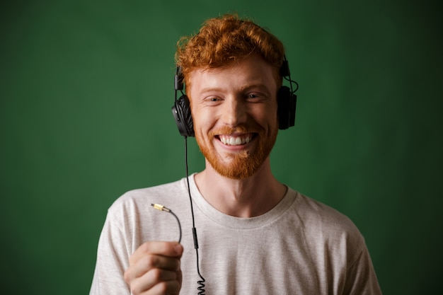 Close-up of young curly readhead hipster holding cord of headphones