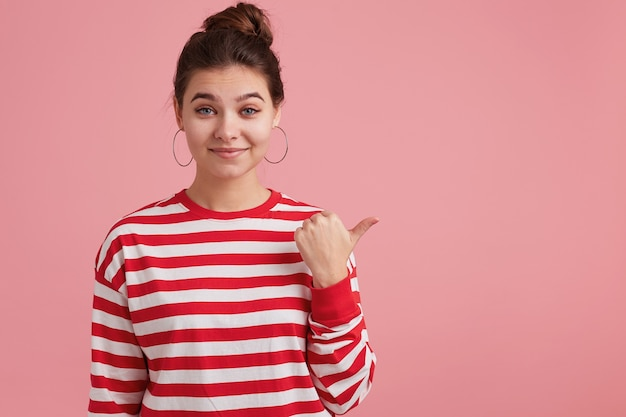 Close up of young cute woman isolated, casually draws your attention to what is on the left, shows with thumb finger on the empty space to copy.