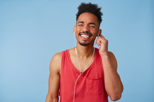 Close up of young dark skinned attractive guy in a red t-shirt , holds earpiece with left hand, closes his eyes and loudly sings a favorite song that plays in headphones, stands.