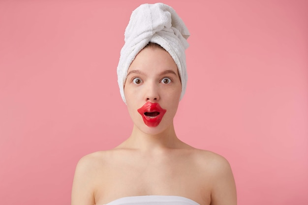 Close up of young dazed lady after spa with a towel on her head, looks, with wide open eyes and mouth, patch for lips, stands.