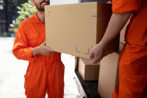 Primo piano sui giovani uomini di consegna che spostano oggetti fuori dall'auto