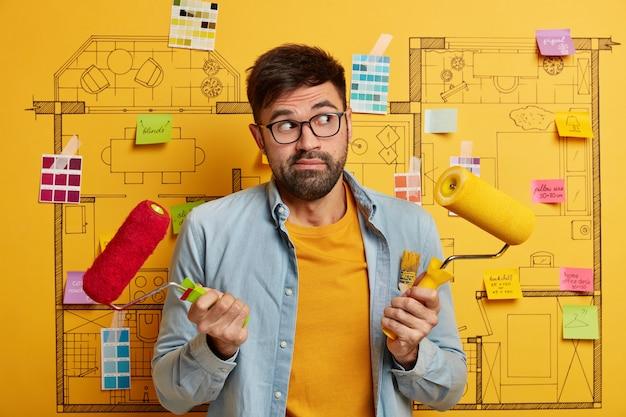 Primo piano sul giovane designer che si prepara a rinnovare accanto allo schizzo del piano generale della casa