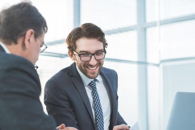 新しいインフォメーションオフィスの就業日を分析する若い従業員をクローズアップ