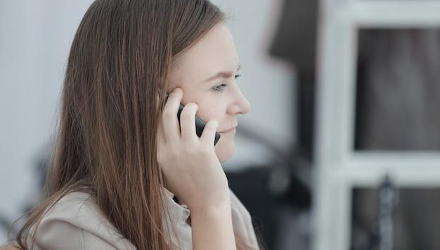 Крупным планом. молодой сотрудник разговаривает по мобильному телефону