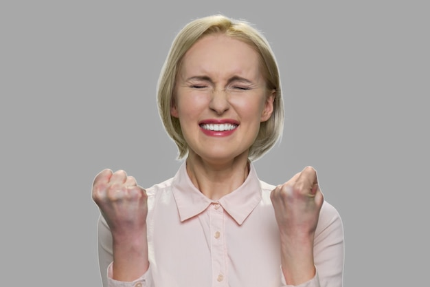 Close up young excited woman celebrating success. lucky successful woman clenched her fists on gray background. personal achievement concept.