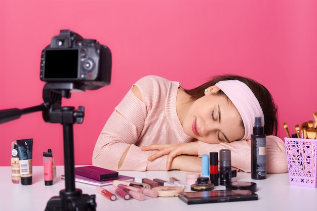 Close up young female blogger, looks tired, falls asleep while recording new video on camera, advertising new beauty products