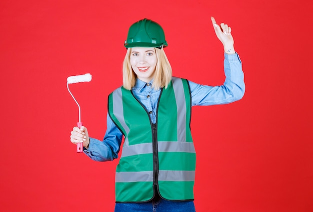 Close up young female builder in uniform, helmet posing and pointing upper to show advertisment