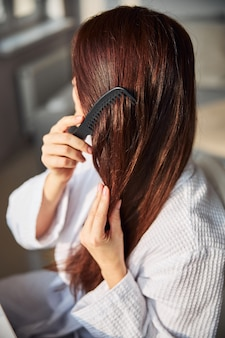 Close up of young female combing her hair