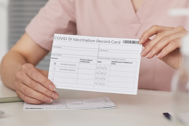 Close up of young female nurse holding vaccination record card while registering patients for covid vaccine in medical center, copy space