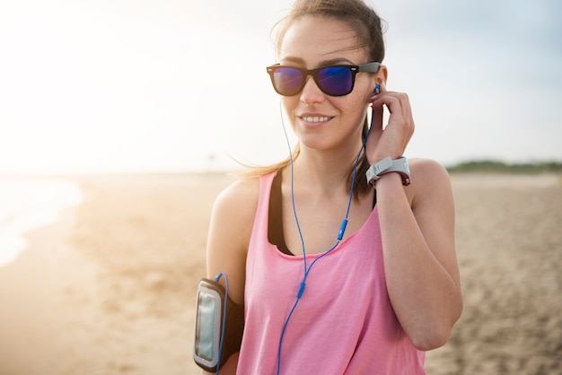 Primo piano su giovane persona in forma fare jogging in riva al mare Foto Gratuite