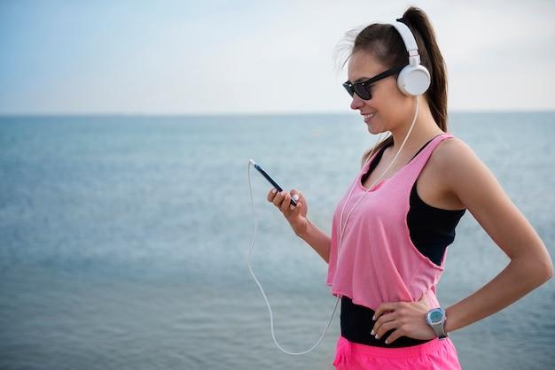 Primo piano su giovane persona in forma fare jogging in riva al mare