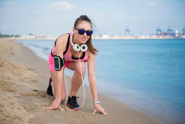 Close up on young fit person jogging by the sea