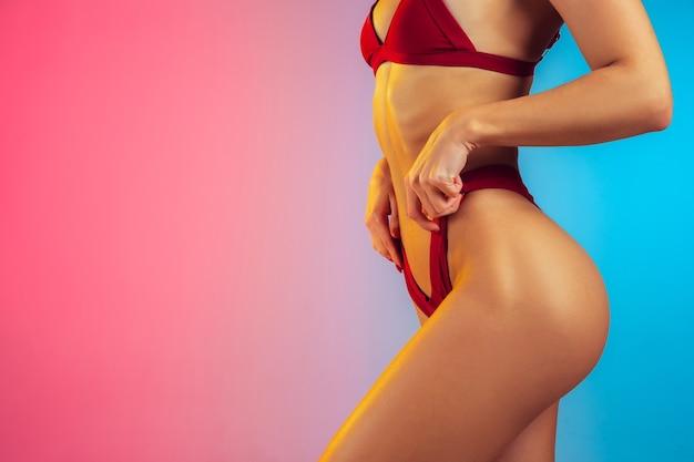 Primo piano di una giovane donna sportiva e in forma in elegante costume da bagno rosso su parete sfumata, corpo perfetto pronto per l'estate