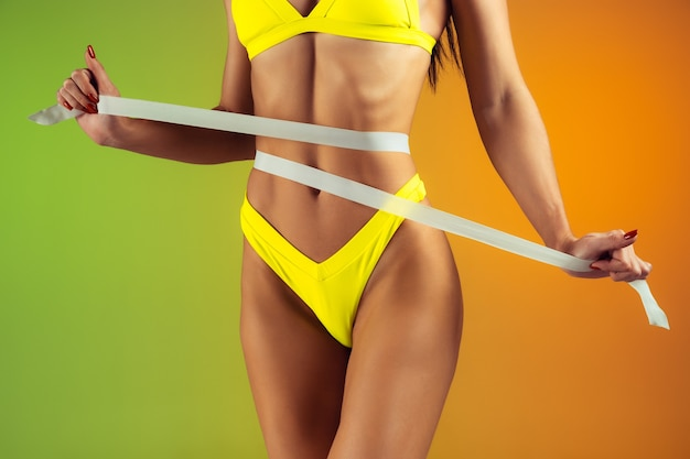 Close up of young fit and sportive woman with measurer in stylish yellow swimwear on gradient.
