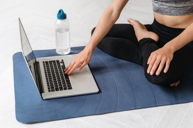 Close up young fit sporty woman wears sportswear search online fitness workout or yoga class using laptop at home.