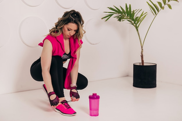 Close up of young fitness woman sitting on the gym floor and putting on her pink sneakers.