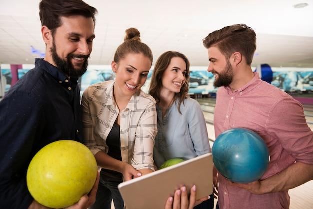 Primo piano su giovani amici che godono di bowling