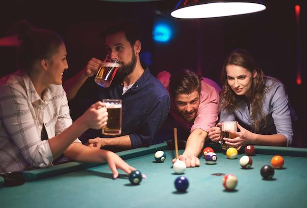 Primo piano su giovani amici che si divertono mentre giocano a biliardo