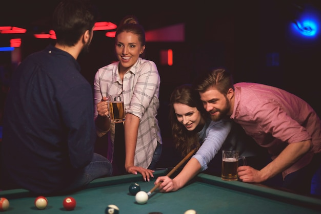 Close up on young friends having fun while playing pool game