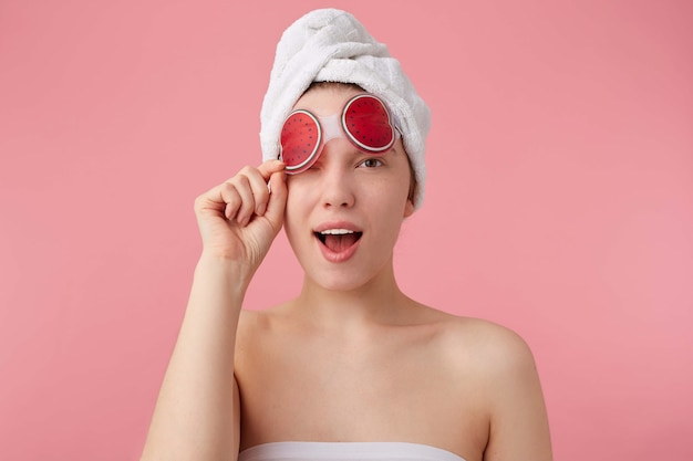 Close up of young funny lady with mask for eyes, after shower with a towel on her head, looks and winks, stands.