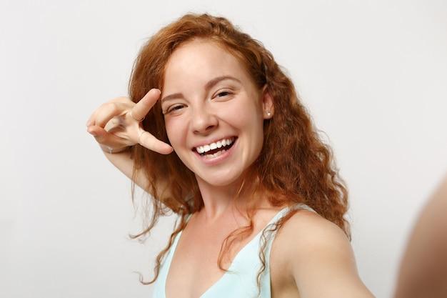 白い背景で隔離のポーズをとってカジュアルな服を着た若い面白い赤毛の女性の女の子を閉じます。人々のライフスタイルの概念。コピースペースをモックアップします。携帯電話で自分撮りをして、勝利のサインを見せます。