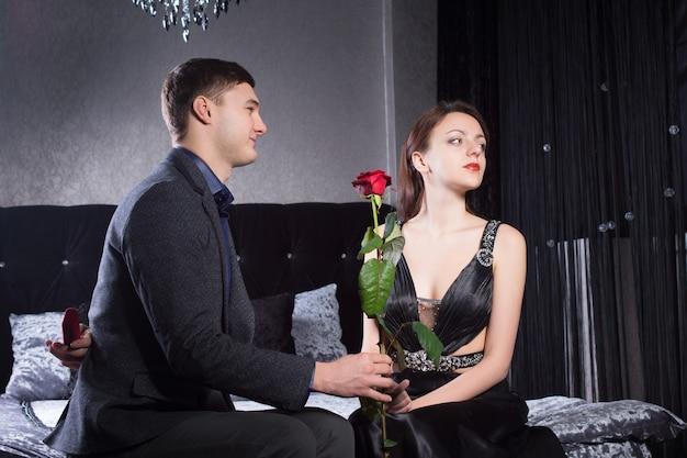 平和の供物として狂ったガールフレンドに赤いバラの花を与える若い紳士を閉じます。