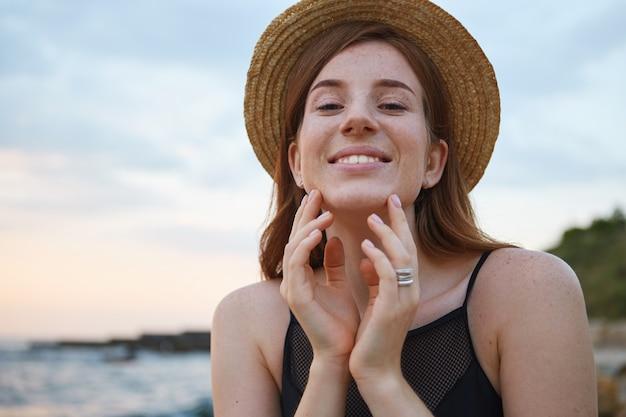 Primo piano di giovane donna di lentiggini carino zenzero cammina sulla spiaggia, indossa un cappello, in generale sorride e tocca cheen, sembra positivo e felice.